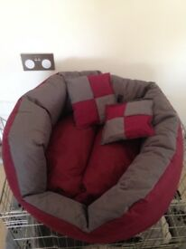 Dog bed as new .Burgundy & grey with 2 little pillows very cute : 2 foot in diameter.