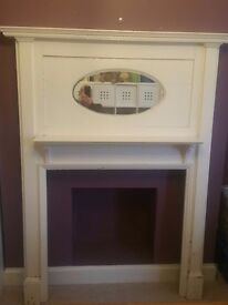 Period fireplace surround - wooden with oval mirror and shelf.