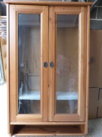 Wooden display cabinet with glass doors and shelves