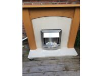 Cream marble fireplace with oak surround and electric fire