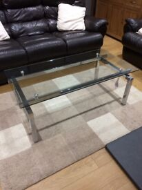Glass coffee table with chrome legs.