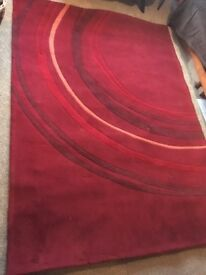 Two red rugs- one large and one medium size acrylic pile rugs