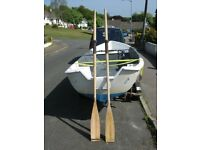 A pair of 7 foot wooden boat oars with leather collars
