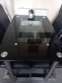 Glass table with shelf underneath + 4 leather chairs