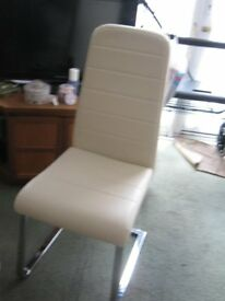 Two white padded vinyl upright chairs