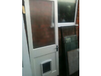 Exterior wooden door with large frosted panel and dog flap
