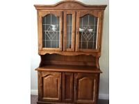 Tall dresser in mid-oak with glass panelled doors above and solid wood cupboard doors below