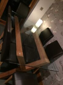 4 chairs and Glass top table, crossed wooden legs, second hand, good condition