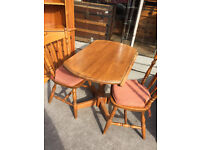 Pine Round Kitchen / Dining Table with sides that fold up and down . And 2 pine chairs