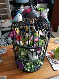 Ornamental cage with birds and butterflies