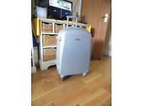 silver hardshell suitcase with four wheels