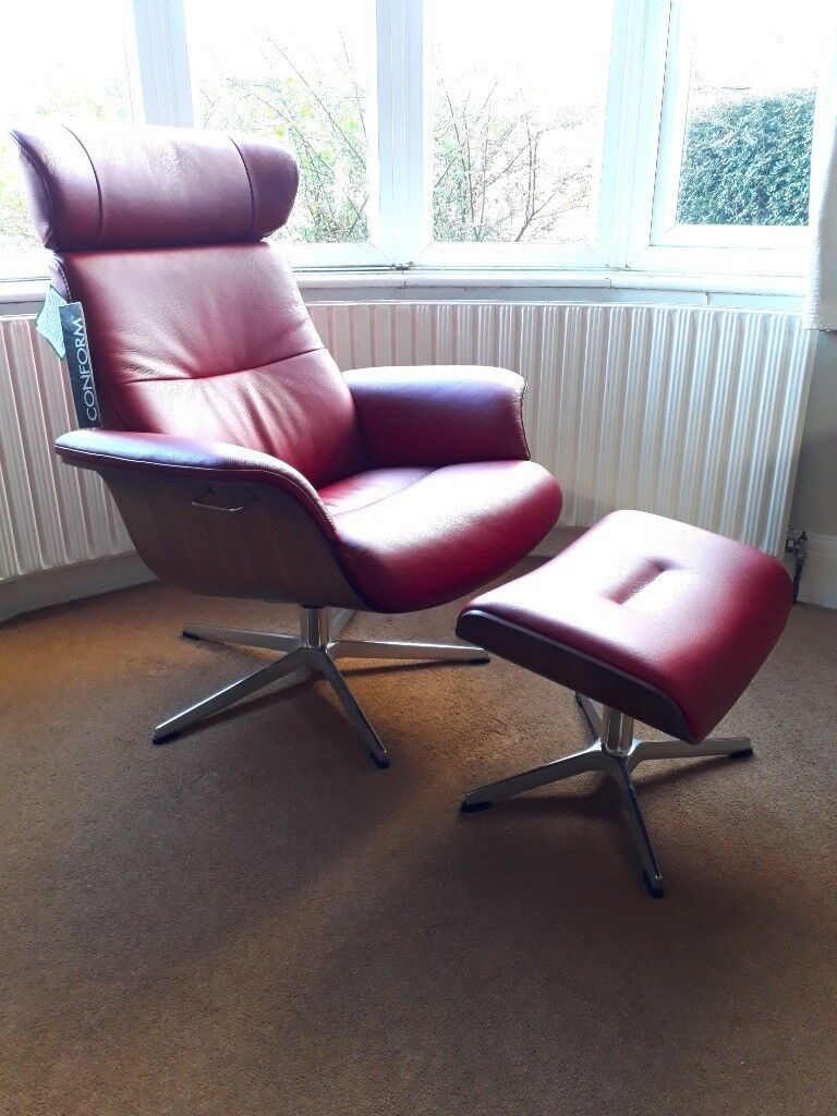 Reclining swivel armchair and footstool in walnut and leather.