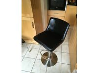 Black leather-look pvc swivel bar stool with back support. Adjustable height