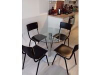 Round glass dining table and four chairs
