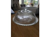Glass cake stand with domed lid.