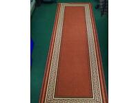 Burnt orange runner rug with gold and cream edge design
