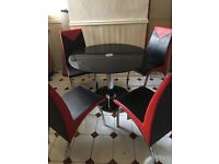 Dining table and four red and black chairs.