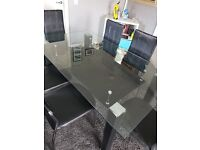 Glass dinning table with 6 black chairs