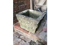 A very heavy square stone plant pot