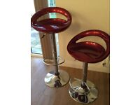 Two red adjustable bar stools