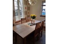 Large solid oak extending dining room table. Comes with 8 matching chairs.