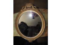 A Victorian oval gilt wood and gesso wall mirror with leaf carved borders