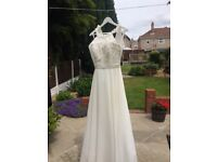 Wedding dress in Ivory in size 10/12. Silky underskirt with chiffon overlay with pearl/sequin bodice