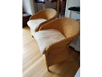 2 wicker chairs and cream cushions
