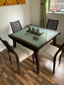Glass top extendable table with 4 chairs.