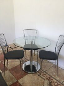 Glass table with chrome base 3 chairs chrome backs and black seats