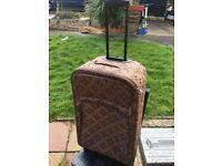 Brown trolley suitcase on wheels.