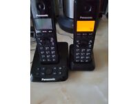 Twin cordless Panasonic telephones with answering machine.