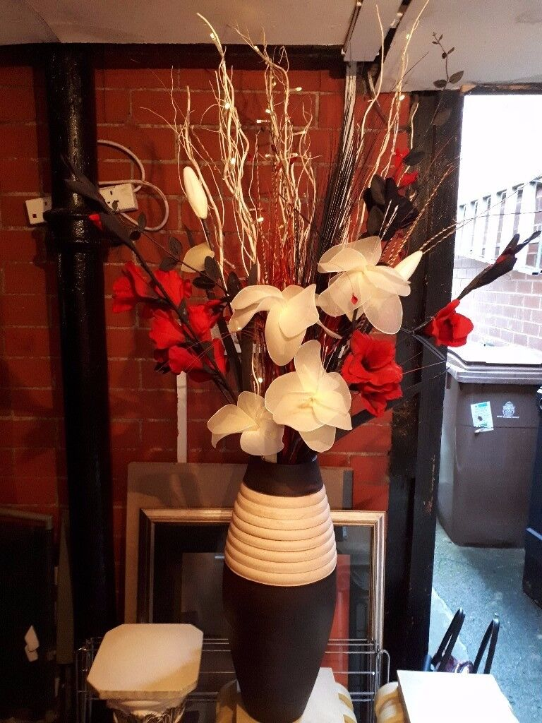 Large vase with dried flower arrangement and fairy lights.