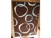 Rug / mat, brown with cream/pale blue pattern, 115cm x 160 cm approx