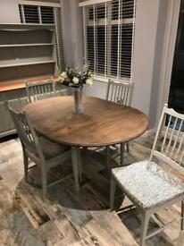 Grey extending dining room table and four chairs