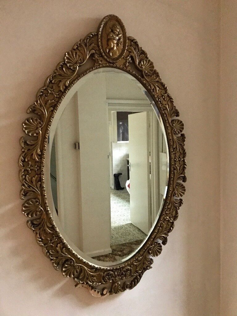 A highly detailed gold framed antique oval wall mirror