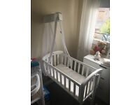 White wooden rocking baby cradle with bumper, quilt and matching drapes.
