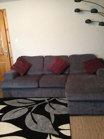Grey fabric 4 seater sofa with chaise lounge to the left