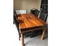 Wooden extendable table & 4 chairs. Stain on table and chairs show wear and tear.