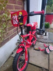 Red bike with stabilisers
