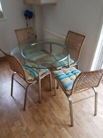 Glass round Table with 4 chairs and teal seat cushions Collection nw7 london.