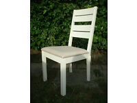 A brand new white chair with cream padding