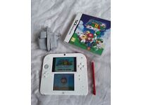 White and red Nintendo 2ds with Super Mario