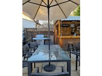 Rattan Garden Table and Seven Chairs stackable with Parasol.