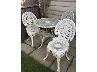 Shabby chic white wrought iron bistro set. Includes table and three chairs,