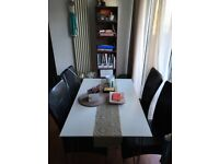 White gloss substantial rectangular dining table and four black chairs. Excellent condition.