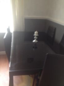 Black table and 6 leatherette chairs toughtened glass some scratches dosnt effect use. Dress it up