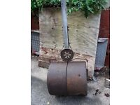 Heavy cast iron garden roller, vintage ornate design.