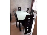 Glass top dining table and six brown chairs