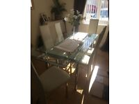 Extendable glass table with 8 chairs lovely condition quick sale £200 tell 07967600386